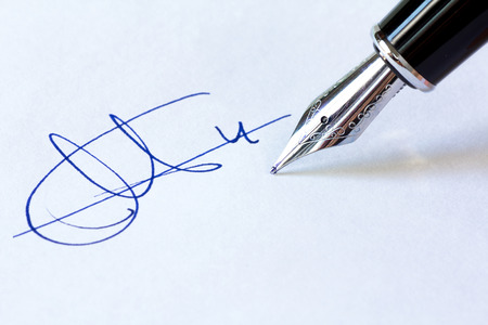 Close up shot of a fountain pen and a signature isolated on white background.