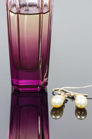 parfum: Parfum bottle and pearl earrings. Stock Photo