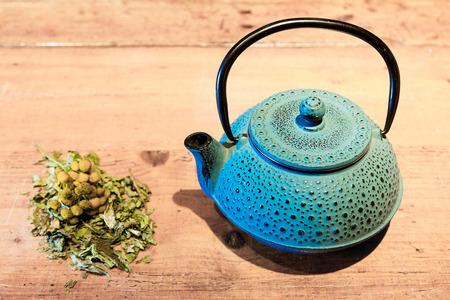 chamomile tea: Blue ceramics teapot, chamomile and tea leaves.