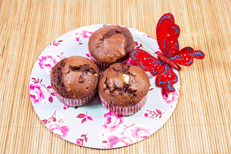 ornated: Chocolate muffins in a ornated plate and red butterfly Stock Photo