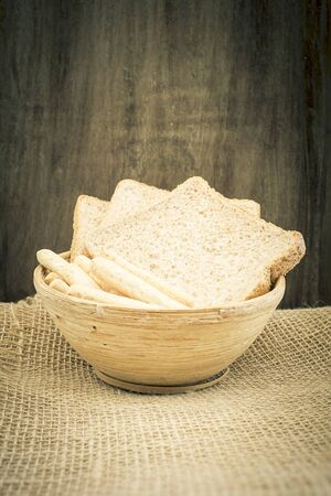 sliced bread: Sliced bread and breadsticks in a wooden bowl