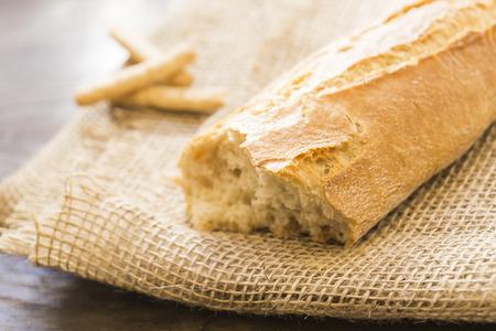 gressins: Baguette fraîche et quelques bâtons sur le tissu de jute