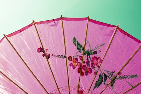 directly below: Directly below shot of an ornated pink umbrella