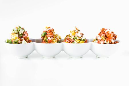 popcorn bowls: Sweet colorful popcorn in bowls over white background