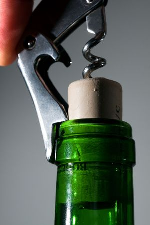 Pulling a cork with a corkscrew.