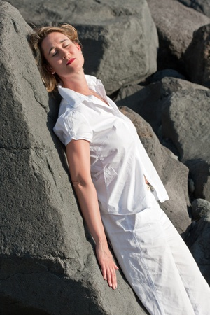 A woman is enjoying the warm sun on a beach.