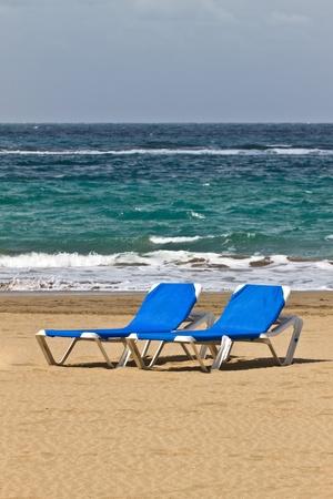 Blue sunchairs on a beach.