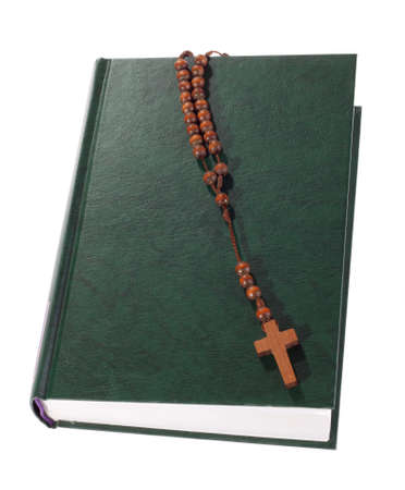 Wooden rosary on the Bible, isolated on white photo
