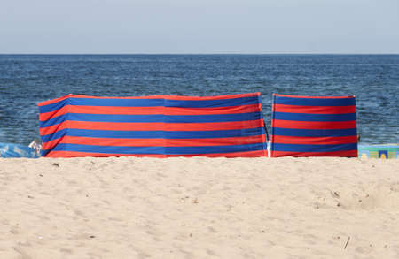 Red and blue striped windbreak at the beach Stock Photo