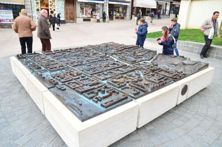 located: Zagreb, Croatia. 14 Mar 2015. Tourists and citizens visit scale model Zagreb Welcomes You by sculptor Damir Matausic. Scale model located at the crossroads of Bakaceva and Cesarceve streets near the Cathedral