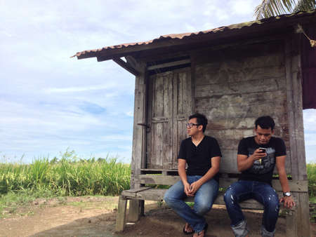 beside: men sitting and waiting at the wood cabin beside paddy field Stock Photo