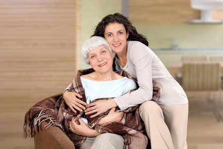 grandmother: elderly woman and her daughter sitting in a chair with a blanket, hug, mother, grandmother Stock Photo