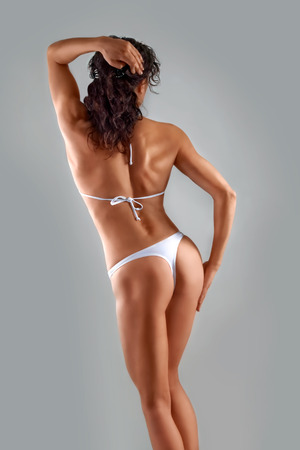 bathing   suit: muscular athletic young slim girl in a white bathing suit on a gray background  Fitness  Muscular body  Backs   Stock Photo