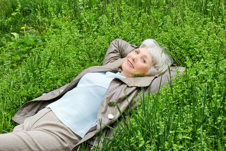 Happy smiling elderly woman lying on green grass meadow in spring