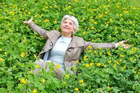 Happy beautiful elderly woman sitting arms outstretched on a glade of yellow flowers in spring Zdjęcie Seryjne