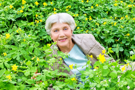Happy beautiful elderly woman sitting on a glade of yellow flowers in spring Zdjęcie Seryjne