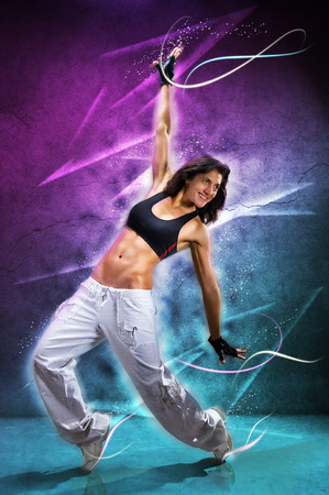 Young beautiful  woman dancing modern dance hip-hop on colorful  background. With lights effect. Zdjęcie Seryjne