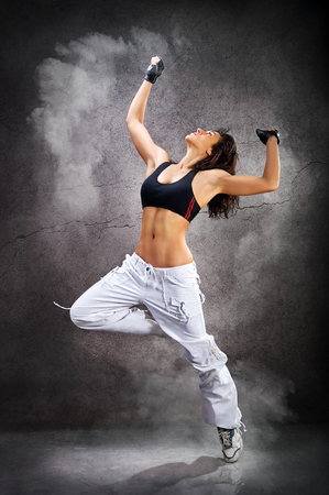 DAnce background: Young beautiful athletic woman dancing modern dance hip-hop on wall background with smoke