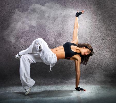 Joven y bella mujer bailando deportivo moderno baile hip-hop en la pared de fondo con el humo Foto de archivo - 44702232