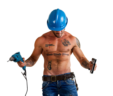 builder bodybuilder with tattoos making repairs with a drill on a white background Zdjęcie Seryjne