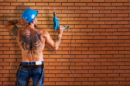 builder bodybuilder with tattoos making repairs drill against the backdrop of a brick wall Zdjęcie Seryjne