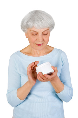 charming elderly woman applying cosmetic cream on her face for facial skin care on a white background Zdjęcie Seryjne
