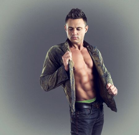 Sexy fashion portrait of male model in stylish clothes with muscular body. Color toned in a trendy modern style