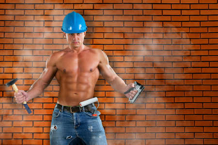 erector: portrait of confident young beautiful handyman with tools on the background wall. House renovation service. Stock Photo