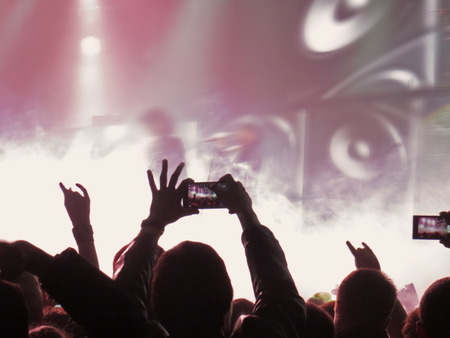 Abstract blurred concept image. Crowd surfing during a musical performance. Hand fans during a concert in fun zone people taking photographs with touch smart phone during a music entertainment public concert Zdjęcie Seryjne