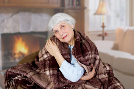Happy beautiful elderly woman sits covered with a blanket in the room. mother. grandmother