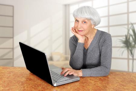 elegant elderly senior woman using laptop computer communicates at home