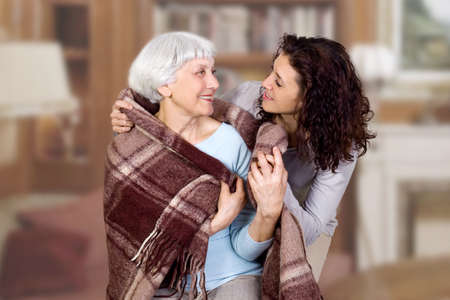 elderly woman and her daughter sitting in a chair with a blanket, hug. mother. grandmother