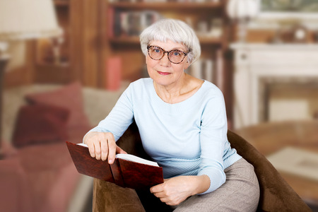 Happy beautiful elderly woman with book and glasses sitting in a chair. mother. grandmother