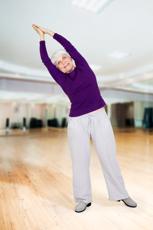 charming beautiful elderly woman doing exercises while working out playing sports in fitness training room Zdjęcie Seryjne
