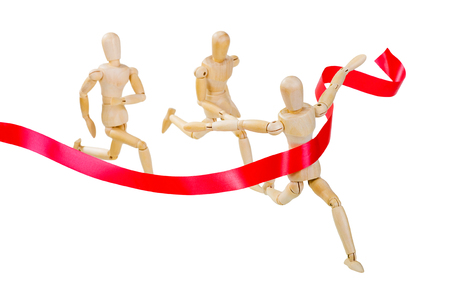 Wooden figure of a man running a leader on a white background with red ribbon. Focus on the leader