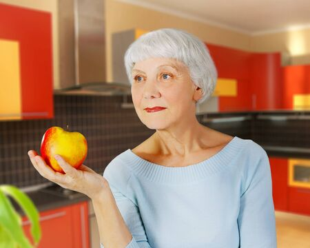elderly woman  senior  with red apple in his hand in the kitchen, grandmother