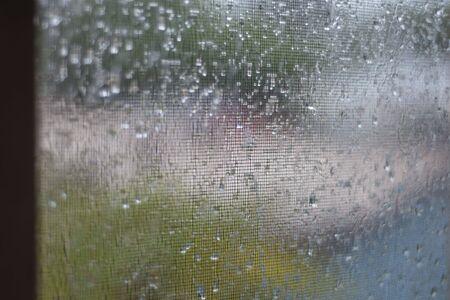 Deszczowy widok przez okno z domami i ulicą zamazaną w tle.