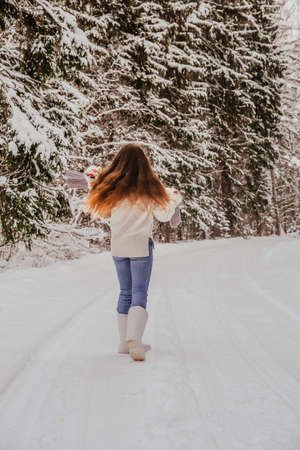red-haired girl in full height in the winter in the forest from the back in white boots and a sweater. Jumping for joy