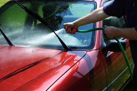 Man washing the car with a water hose photo