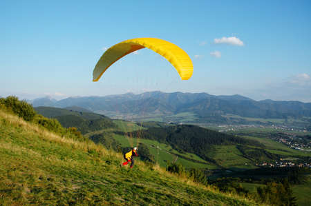 Paraglider with yellow parachute taking off