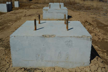 cornerstone: Concrete Foundation Blocks on the Ground. Industrial Zone. Stock Photo