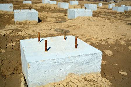Concrete Foundation Construction Area. Concrete blocks on a wet sand ground. Banco de Imagens
