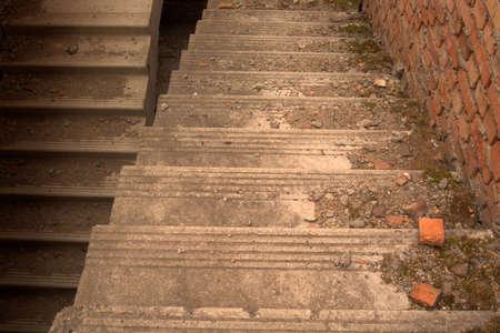bajando escaleras: Cemento bajar escaleras con musgo, piezas de hormigón y ladrillos rotos.