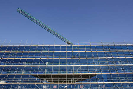 building under construction with blue scaffolding and blue sky