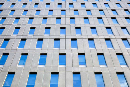 concrete facade of office building with regular pattern of windows reflecting blue sky Stock Photo - 17935773
