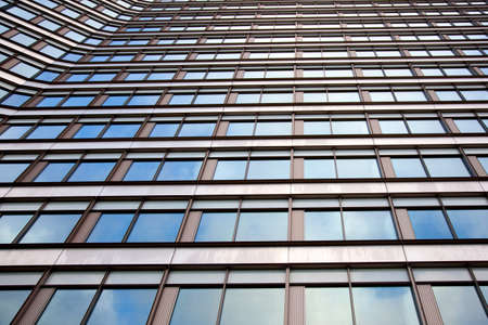 facade of office building with regular pattern windows reflecting white cloud Stock Photo - 17935775