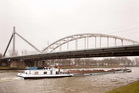 ship in canal transporting sand under bridge in The Netherlands