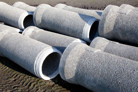 grey concrete pipes waiting to be put under the ground Stock Photo