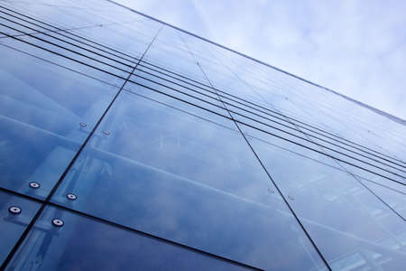 blue modern facade of office building reflecting sky photo