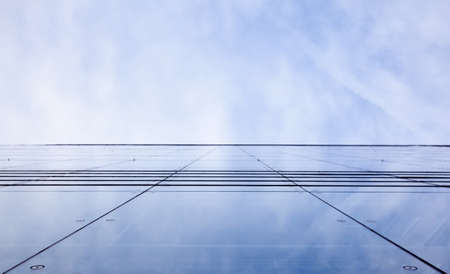 facade of glass and reflection of sky and clouds photo